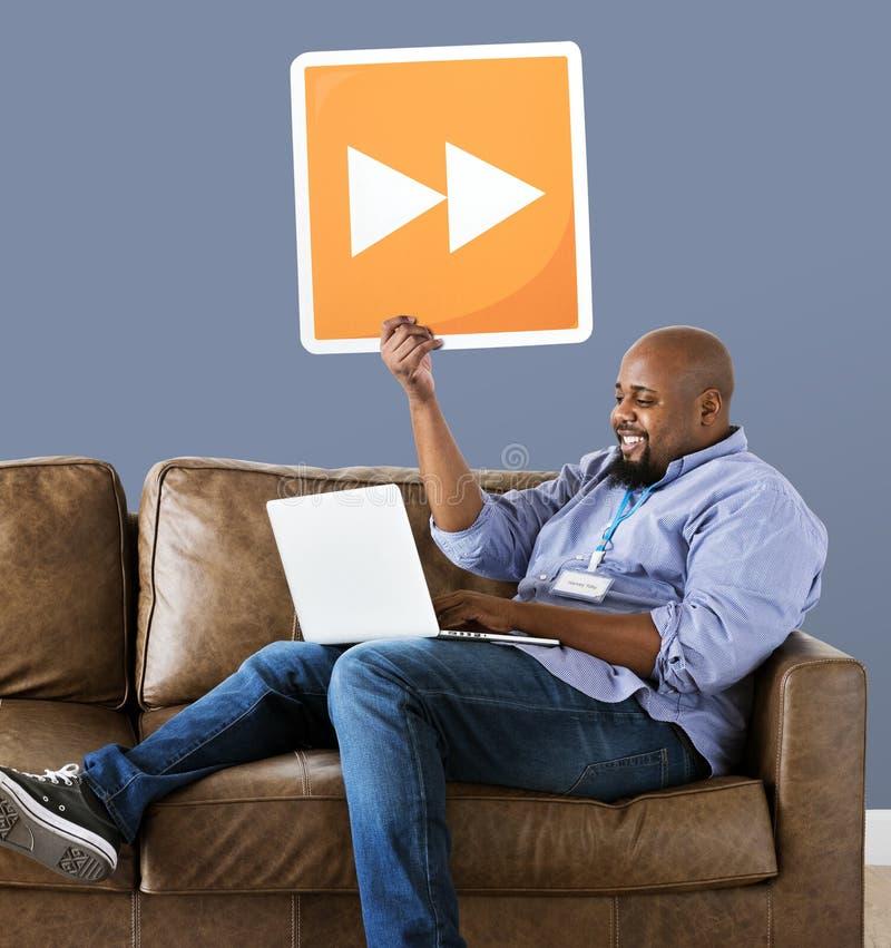 Hombre usando un ordenador portátil y sostener un botón delantero rápido foto de archivo