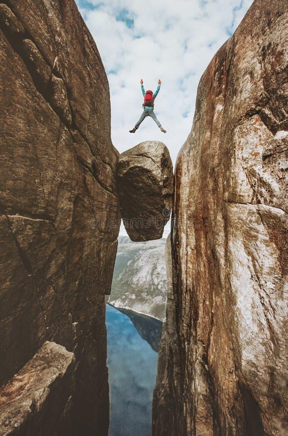 Hombre valiente que salta sobre el viaje extremo de Kjeragbolten en Noruega imagen de archivo