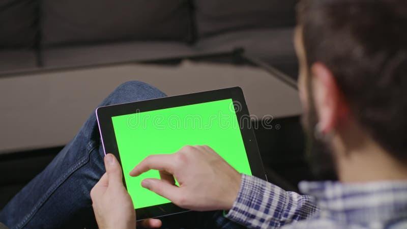 Hombre verde del Tablet PC de Digitaces de la pantalla fotografía de archivo