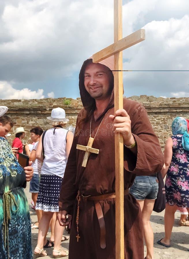 Hombre vestido como sacerdote medieval, monje con una cruz de madera con un personal en su mano y con una cruz de madera en su cu fotos de archivo libres de regalías
