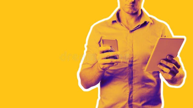 Hombre vestido ocasional en camisa agarrada usando una tableta y un teléfono fotos de archivo