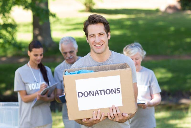 Hombre voluntario feliz que sostiene la caja de la donación fotografía de archivo libre de regalías