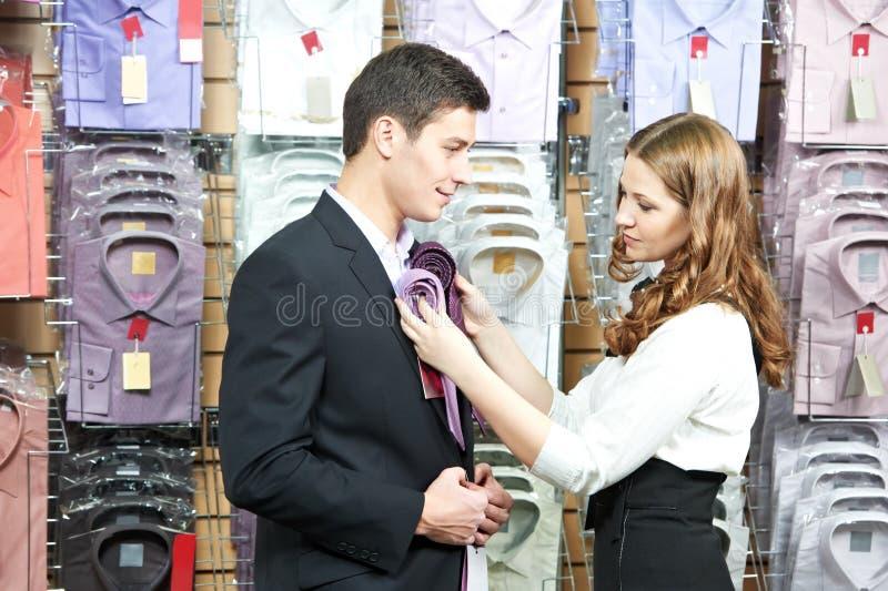 Hombre y ayudante en hacer compras de la ropa de la ropa fotos de archivo
