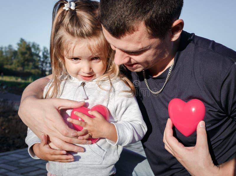 Hombre y bebé que llevan a cabo un corazón del plástico de dos rojos el padre abraza a la hija imagen de archivo