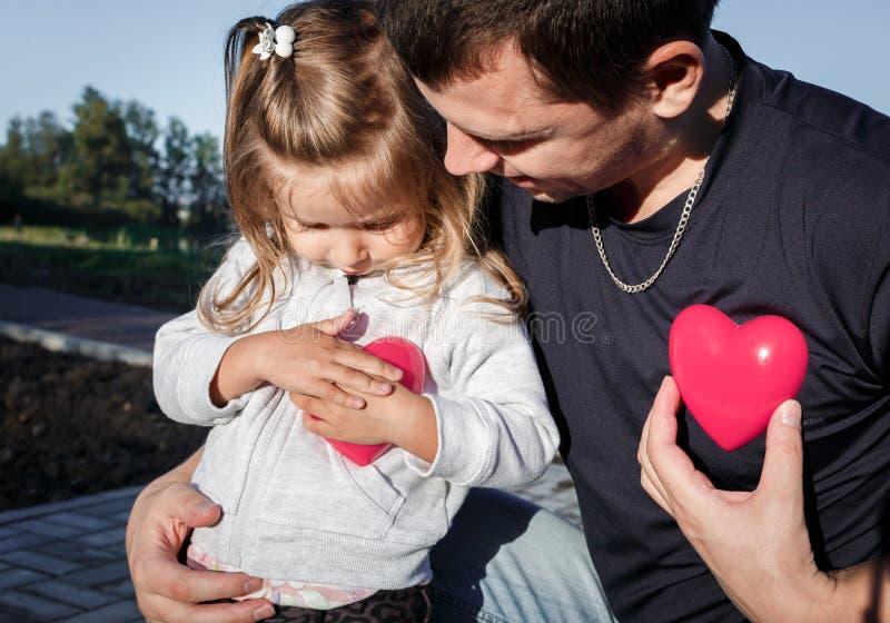 Hombre y bebé que llevan a cabo un corazón del plástico de dos rojos el padre abraza a la hija fotos de archivo libres de regalías