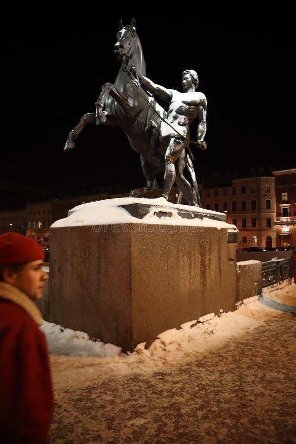 Hombre y caballo del monumento en un puente en el invierno St Petersburg en la noche imagenes de archivo