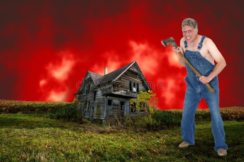 Hombre y casa encantada locos del asesino del hacha de Halloween imagen de archivo libre de regalías