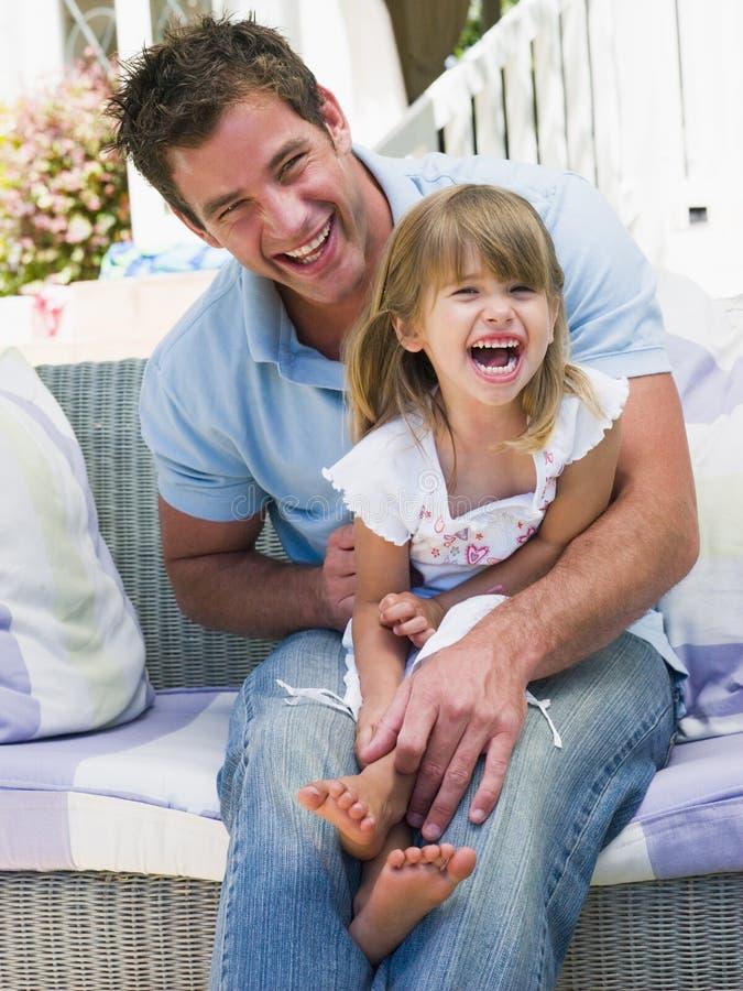 Hombre y chica joven que se sientan en la risa del patio fotografía de archivo libre de regalías