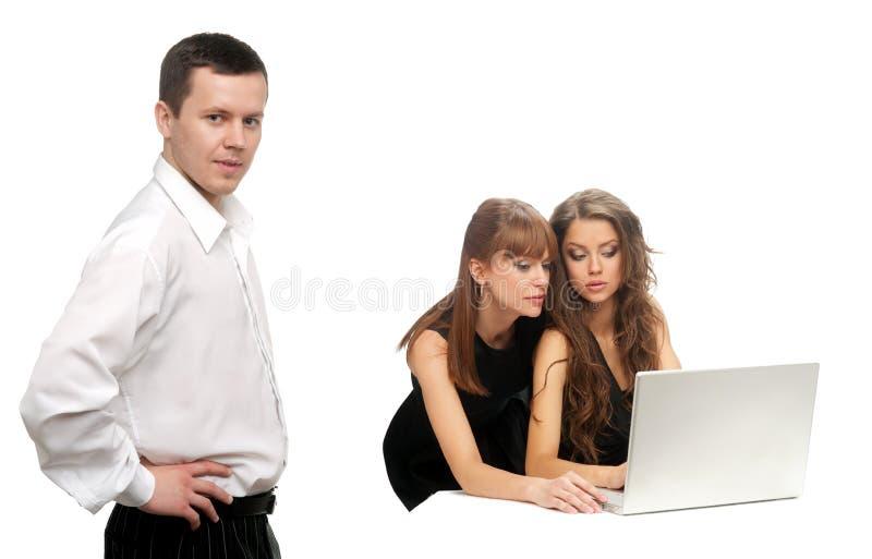 Hombre y dos mujeres con el ordenador foto de archivo libre de regalías