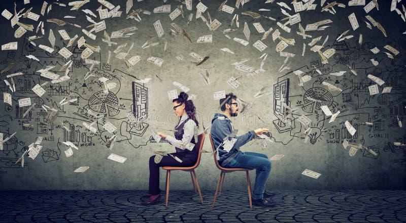 Hombre y empresaria de negocios que trabajan en el ordenador que desarrolla estrategia acertada debajo de la lluvia del dinero foto de archivo libre de regalías
