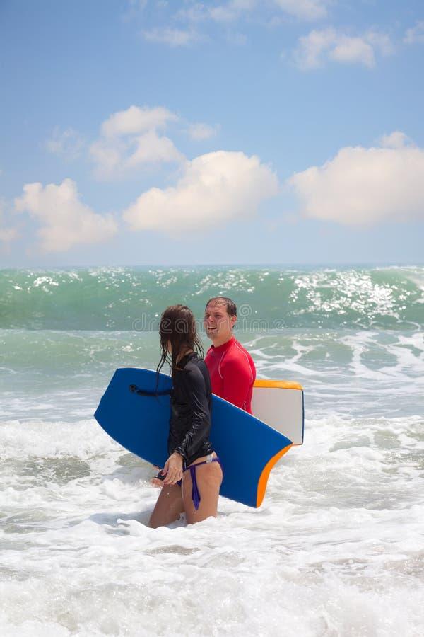 Hombre y la muchacha con una tabla hawaiana imagenes de archivo