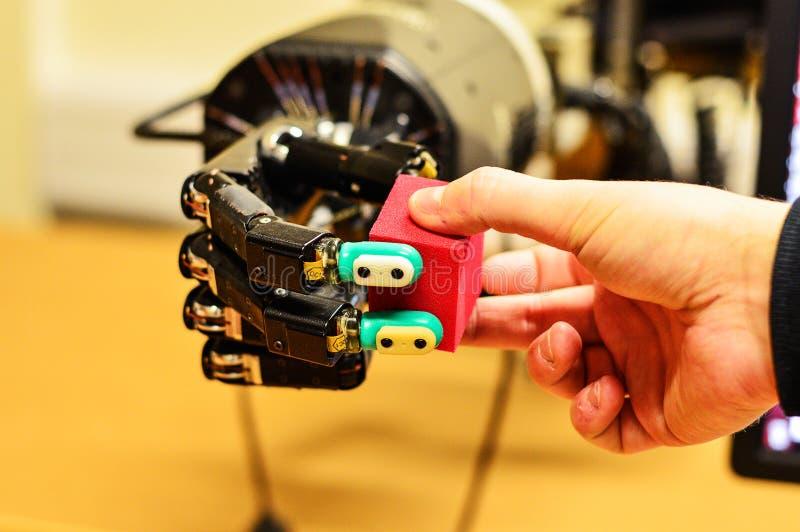Hombre y mano mecánica que sostienen un cubo rojo en el laboratorio de investigación fotos de archivo libres de regalías