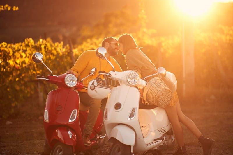 Hombre y muchacha de amor en la vespa que gozan en viaje por carretera romántico fotos de archivo
