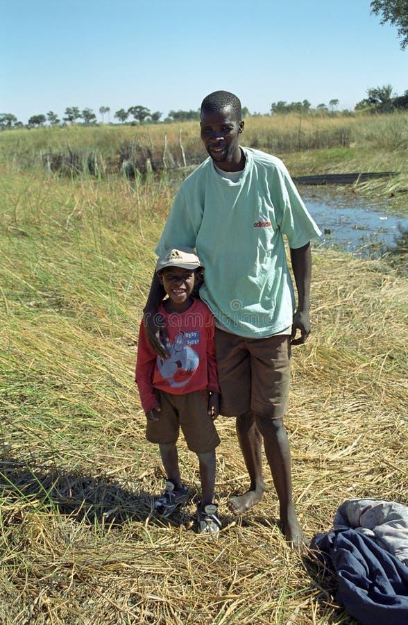 Hombre y muchacho, delta de Okavango, Botswana fotografía de archivo