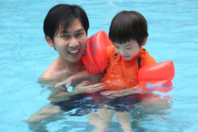 Hombre y muchacho en la piscina foto de archivo