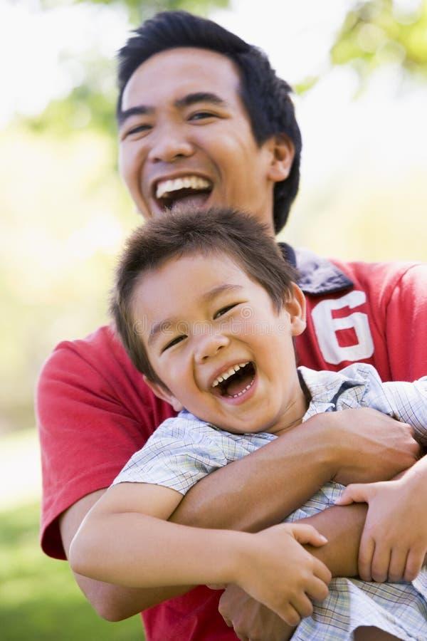 Hombre y muchacho joven al aire libre que abrazan y que sonríen imagen de archivo libre de regalías