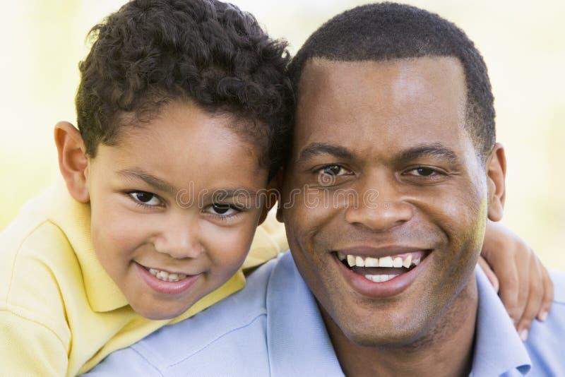 Hombre y muchacho joven al aire libre que sonríen foto de archivo libre de regalías
