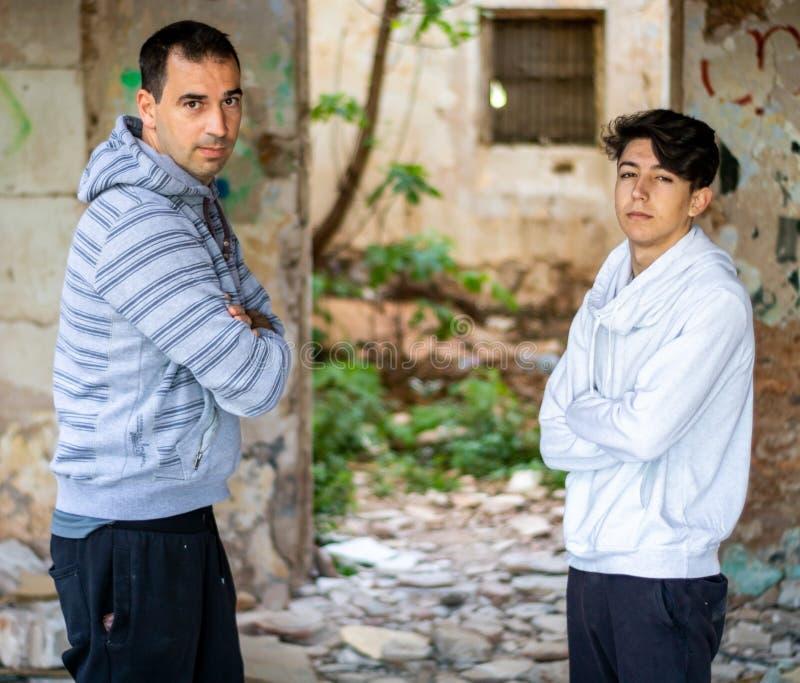 Hombre y muchacho joven en una casa abandonada foto de archivo