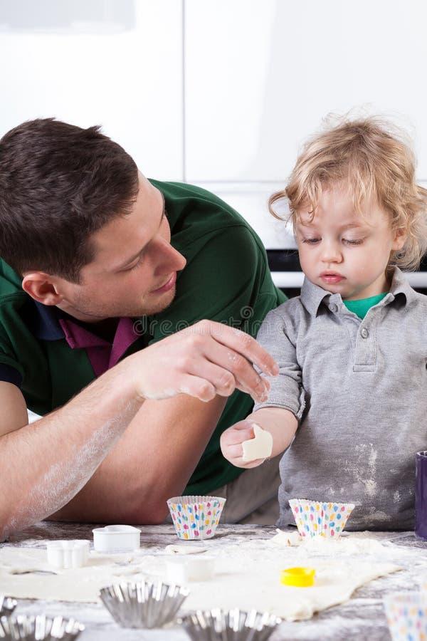 Hombre y muchacho que juegan en cocina foto de archivo