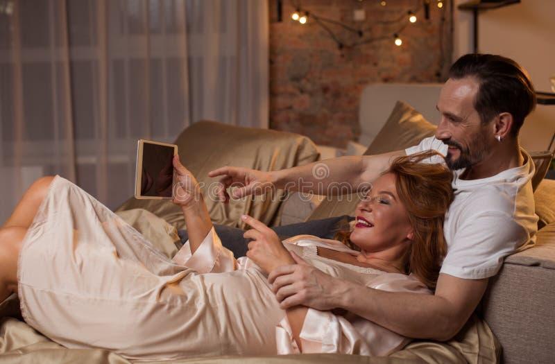 Hombre y mujer alegres que usa el artilugio en casa imagen de archivo