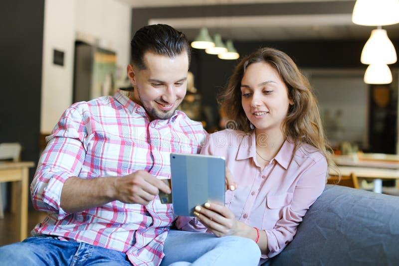 Hombre y mujer americanos jovenes que usa la tableta en el café con la tarjeta de débito fotos de archivo libres de regalías