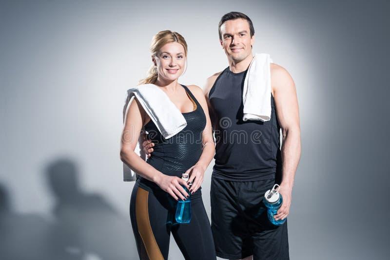 Hombre y mujer atléticos con las toallas que sostienen las botellas del deporte fotografía de archivo libre de regalías
