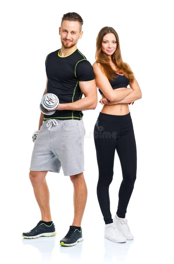 Hombre y mujer atléticos con pesas de gimnasia en el blanco foto de archivo