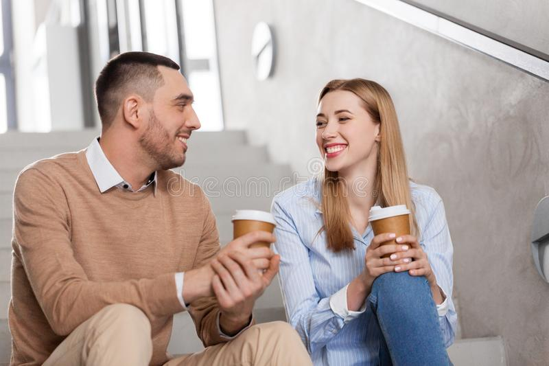 Hombre y mujer con café que hablan en las escaleras de la oficina foto de archivo