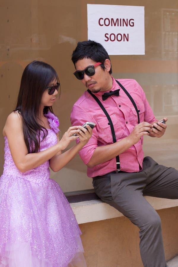 Hombre y mujer con el teléfono móvil a disposición imagen de archivo libre de regalías