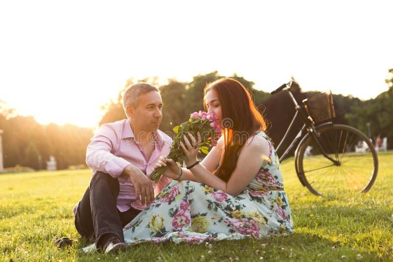 Hombre y mujer con las flores que se sientan cerca de la bicicleta foto de archivo