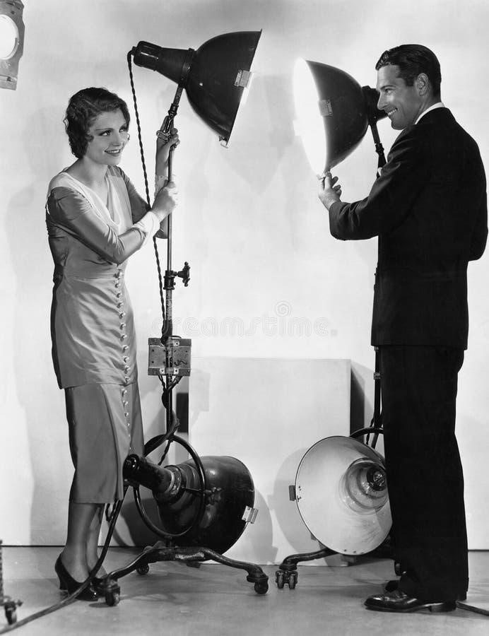 Hombre y mujer con las luces en soportes fotografía de archivo