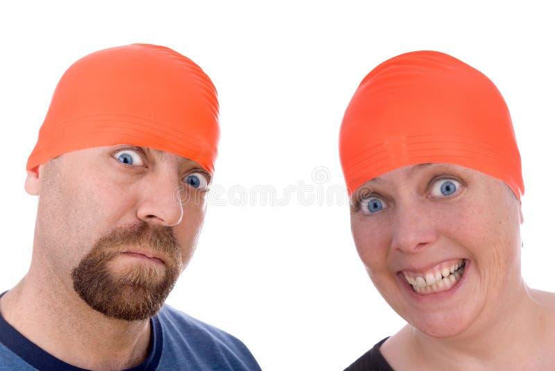 Hombre y mujer con los casquillos anaranjados de una nadada fotografía de archivo