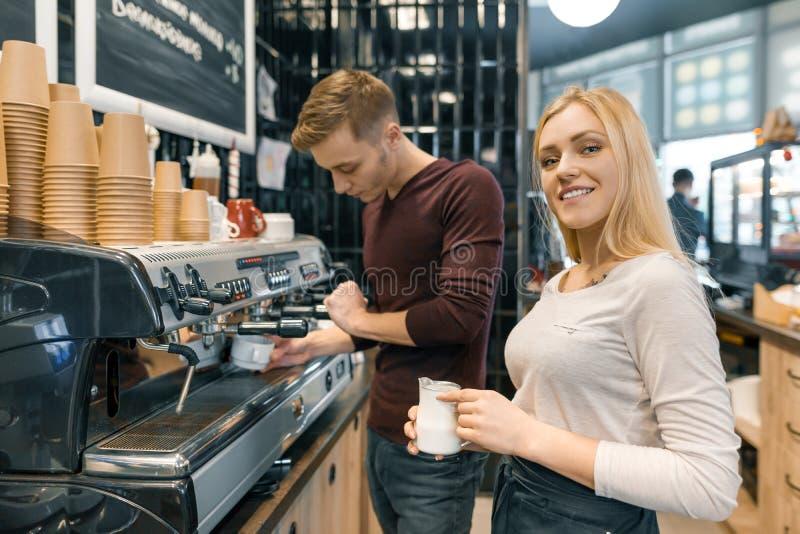 Hombre y mujer de Barista que hacen el café, par de la gente joven que trabaja en cafetería foto de archivo