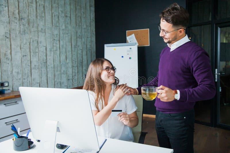 Hombre y mujer de dos personas en la oficina con la pantalla de ordenador y la tarjeta de crédito fotografía de archivo