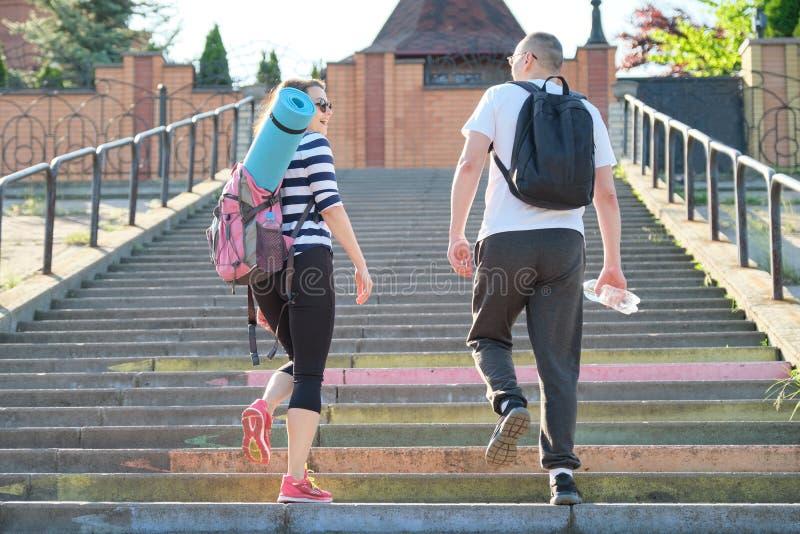 Hombre y mujer de mediana edad en caminar que habla de la ropa de deportes foto de archivo