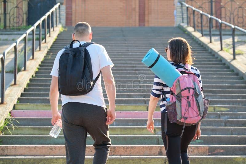 Hombre y mujer de mediana edad en caminar que habla de la ropa de deportes fotografía de archivo