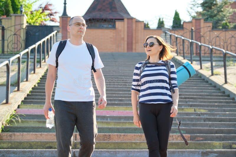 Hombre y mujer de mediana edad en caminar que habla de la ropa de deportes imagen de archivo libre de regalías