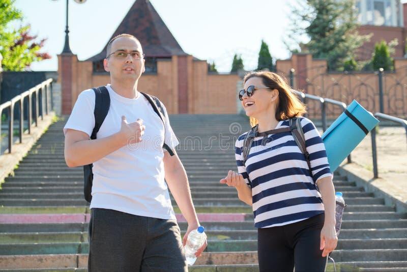 Hombre y mujer de mediana edad en caminar que habla de la ropa de deportes imagen de archivo