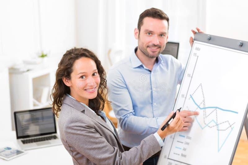 Hombre y mujer de negocios, analizando el stats en un cartón foto de archivo libre de regalías
