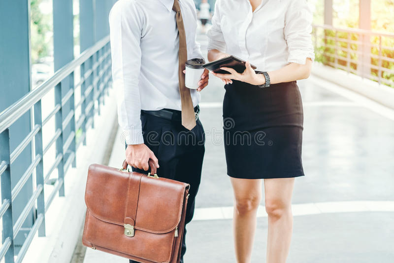 Hombre y mujer de negocios con la tableta que se coloca que habla y fotografía de archivo libre de regalías