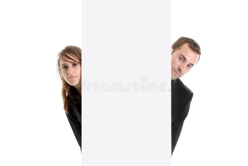 Hombre y mujer de negocios que ocultan detrás de un espacio del anuncio fotografía de archivo