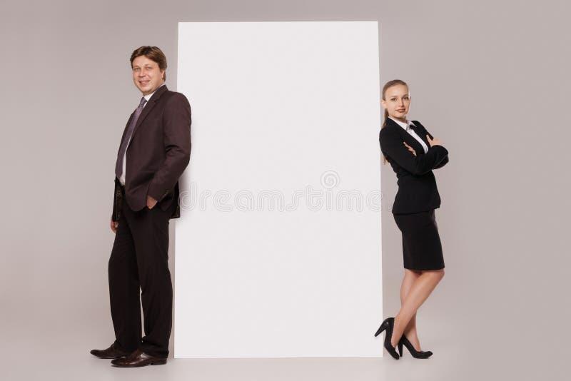 Hombre y mujer de negocios que se colocan sobre bandera en blanco imagen de archivo