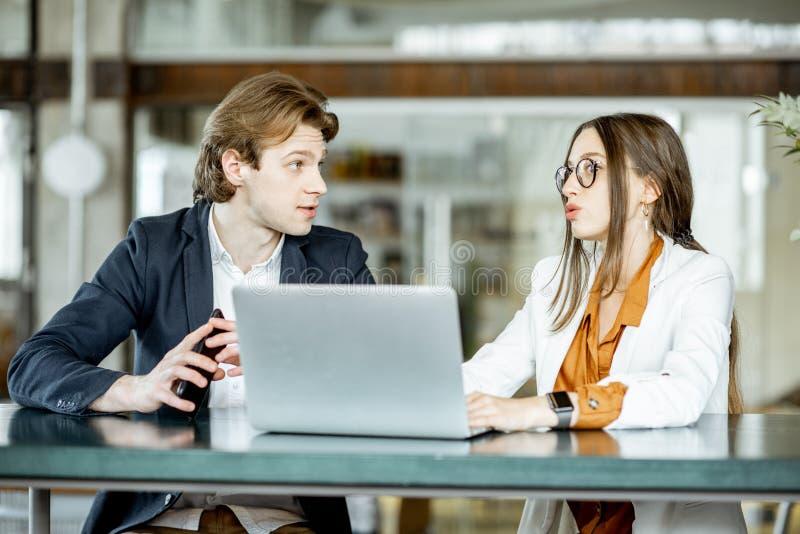 Hombre y mujer de negocios que trabajan con el ordenador port?til dentro fotos de archivo libres de regalías