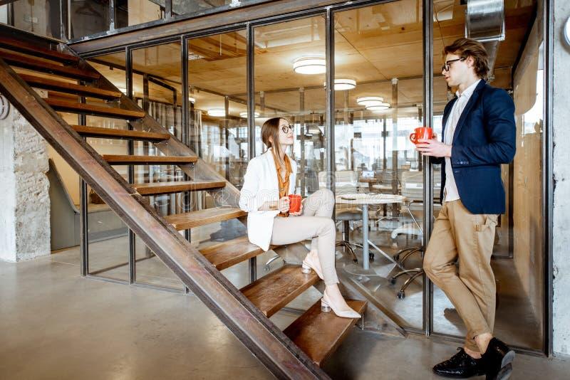Hombre y mujer durante el descanso para tomar caf? en la oficina imagen de archivo