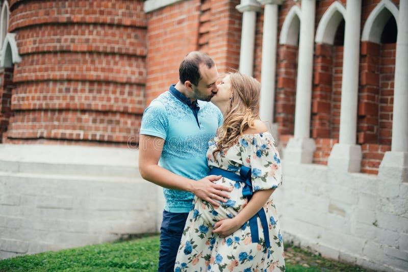 Hombre y mujer embarazada, en un par amoroso en el parque imagenes de archivo