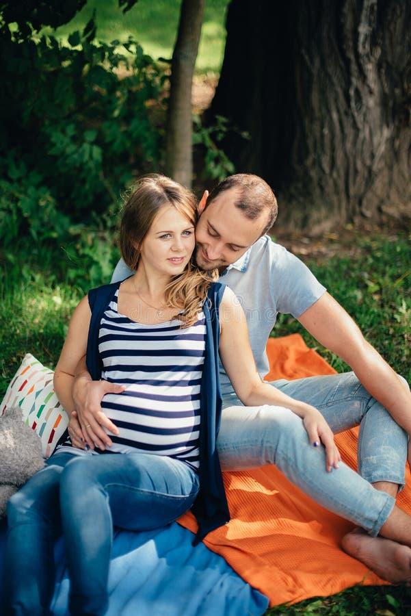 Hombre y mujer embarazada, en un par amoroso en el parque foto de archivo libre de regalías