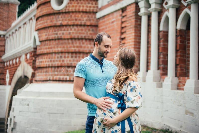 Hombre y mujer embarazada, en un par amoroso en el parque foto de archivo