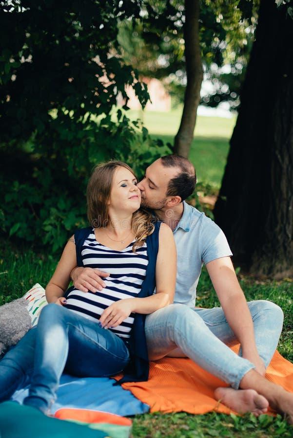 Hombre y mujer embarazada, en un par amoroso en el parque fotografía de archivo