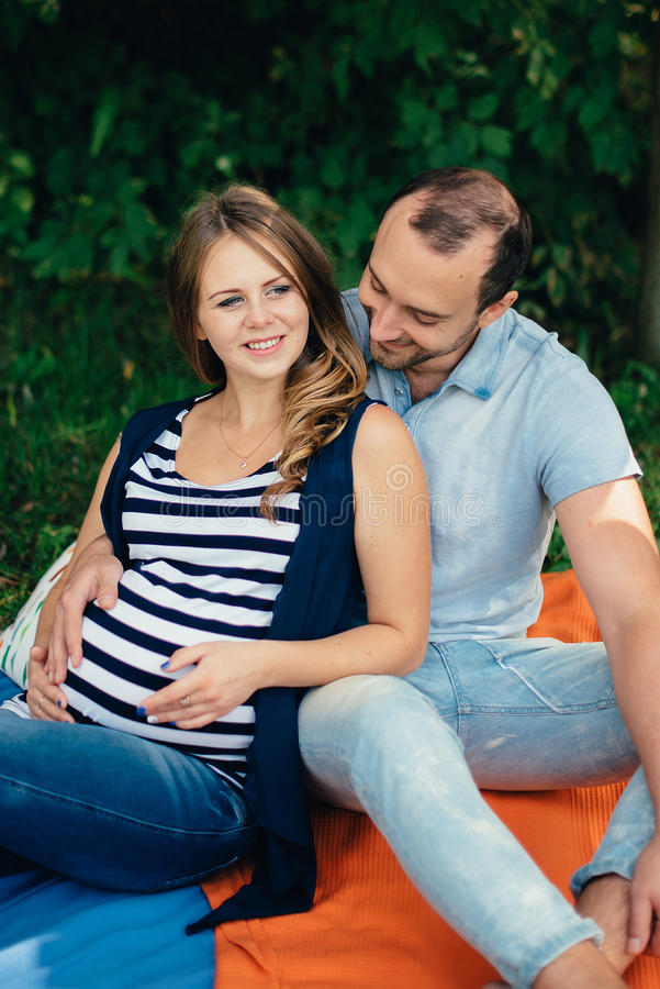 Hombre y mujer embarazada, en un par amoroso en el parque fotos de archivo