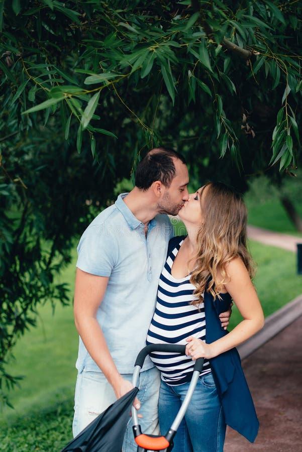 Hombre y mujer embarazada, en un par amoroso en el parque imágenes de archivo libres de regalías